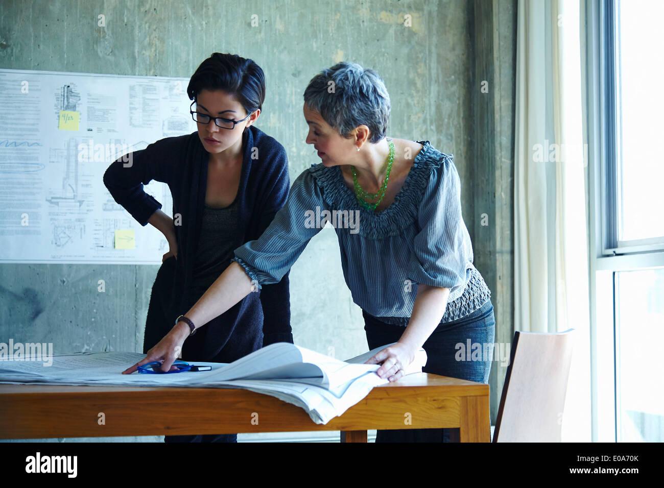 Zwei Geschäftsfrauen Studium der Baupläne im Büro Stockbild