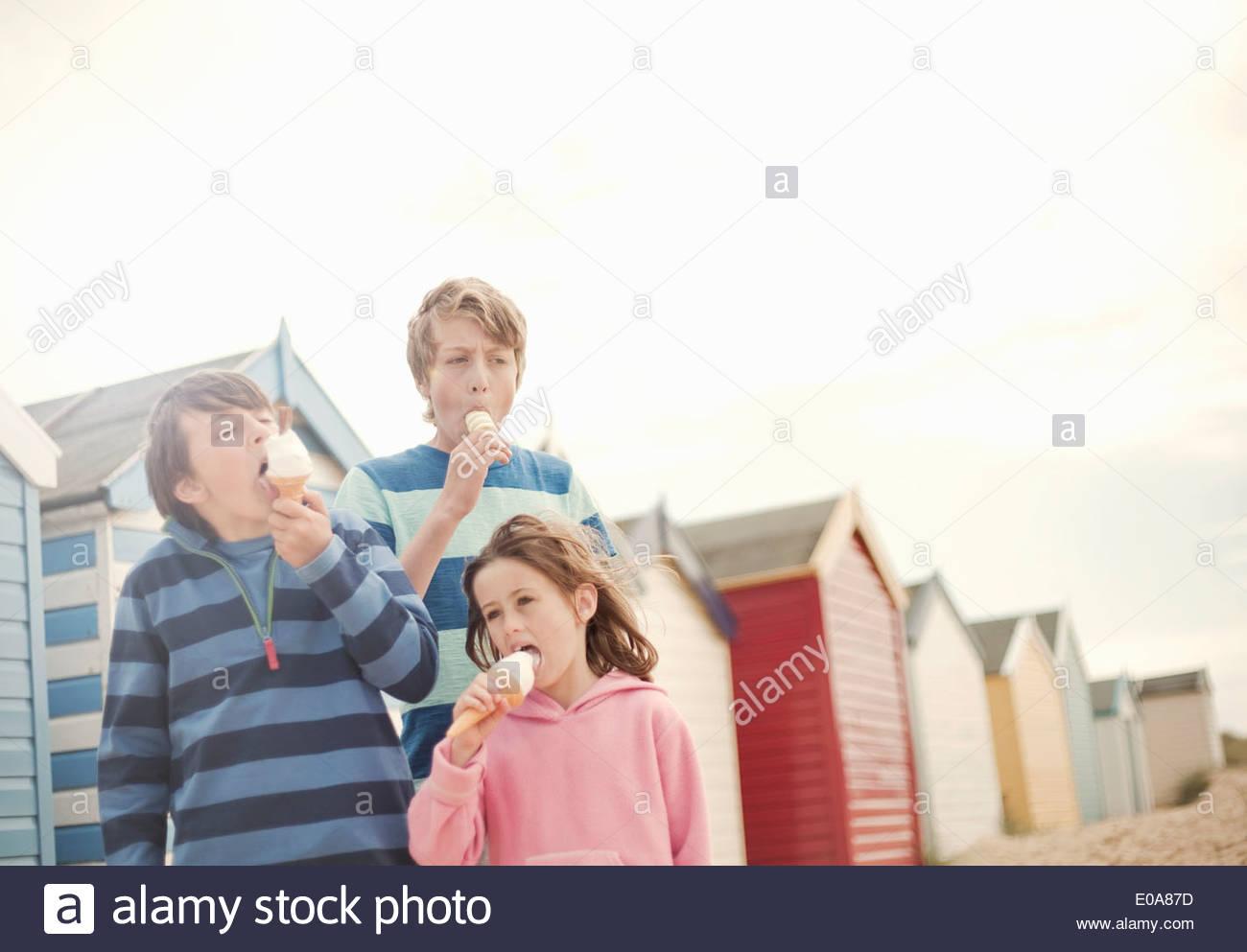 Drei Kinder neben Strandhütten essen Eiscreme-Kegel, Southwold, Sussex, UK Stockbild
