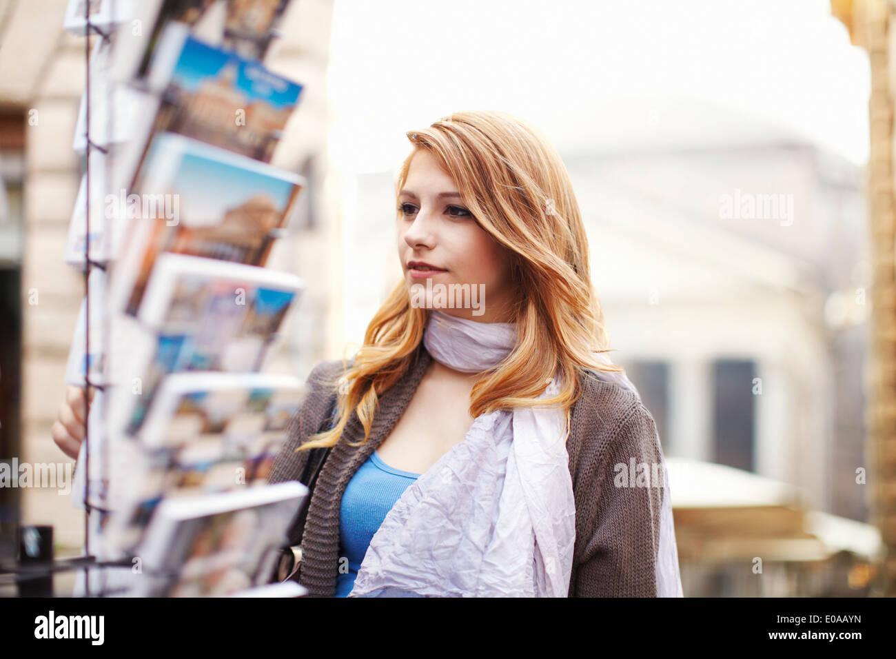 Junge Frau Blick auf Postkarten, Rom, Italien Stockbild