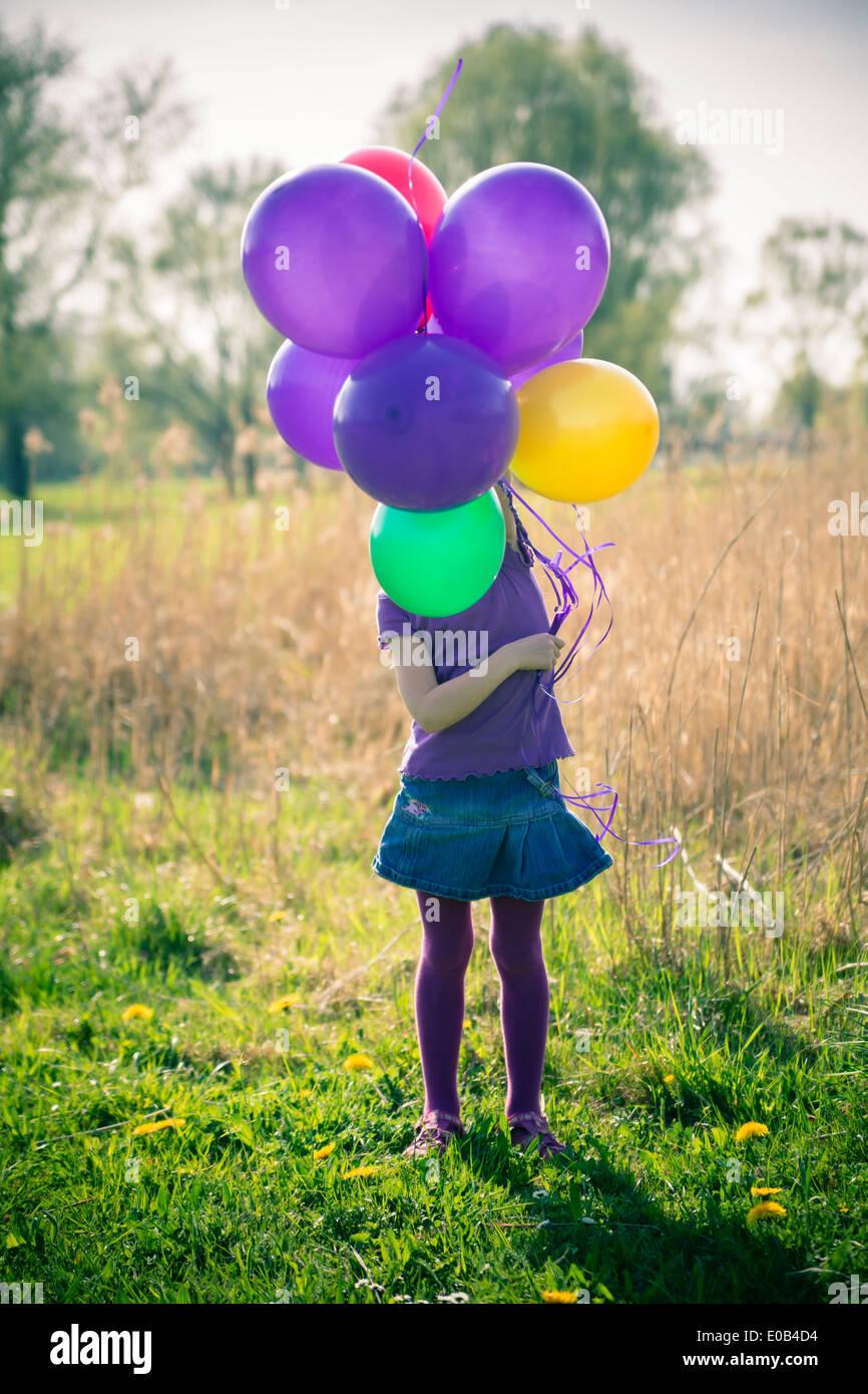 Kleines Mädchen Gesicht versteckt hinter Luftballons Stockbild