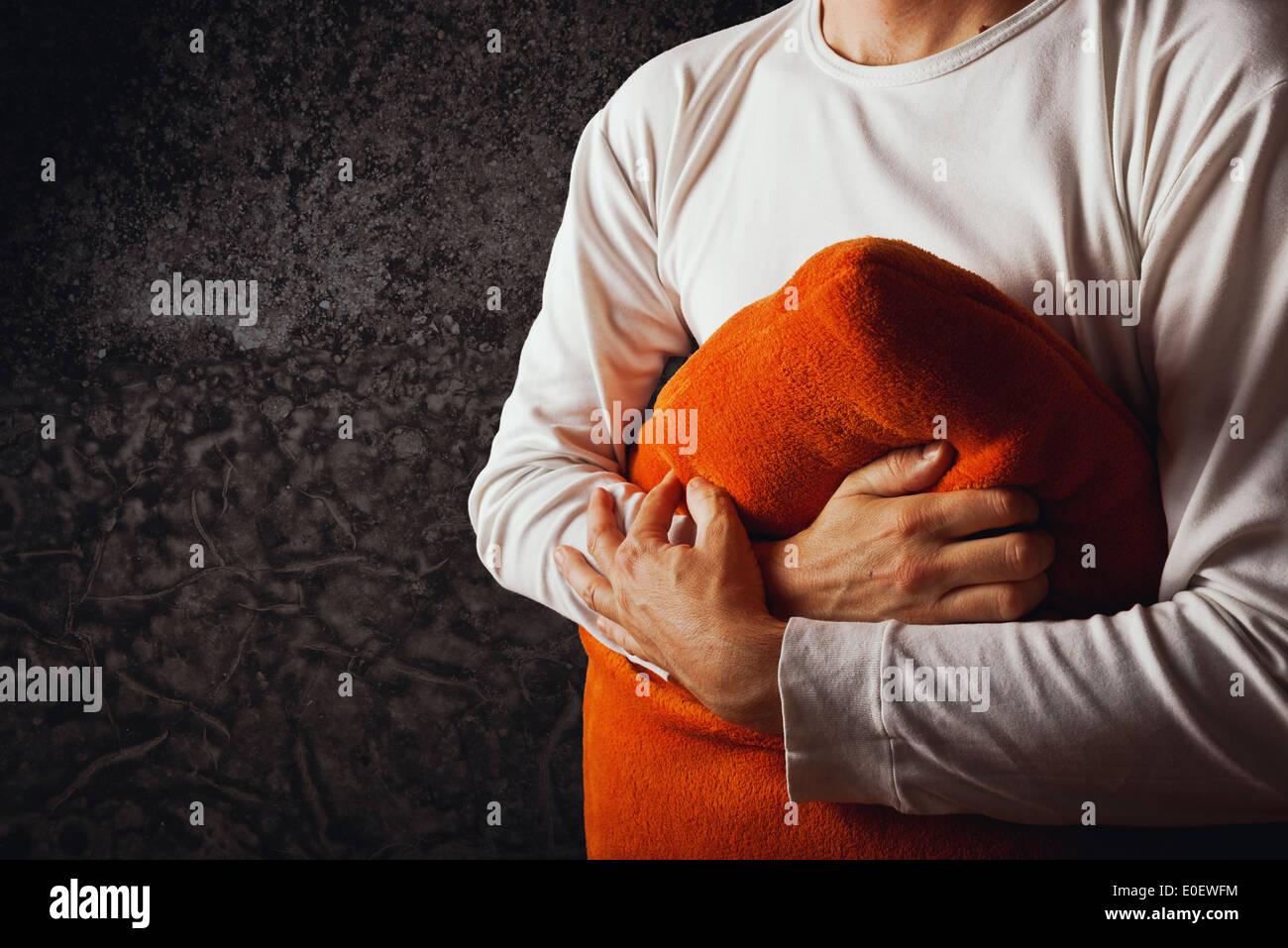 Mann umarmt orange Kissen im dunklen Raum. Konzept von Kummer, Traurigkeit und Depression. Stockbild