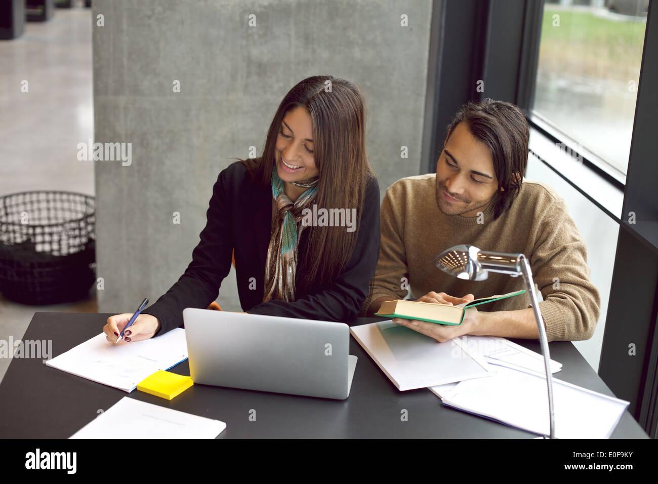 Junge Studenten Notizen von Fachbücher für das Studium. Junger Mann und Frau, die mit Büchern und Stockbild