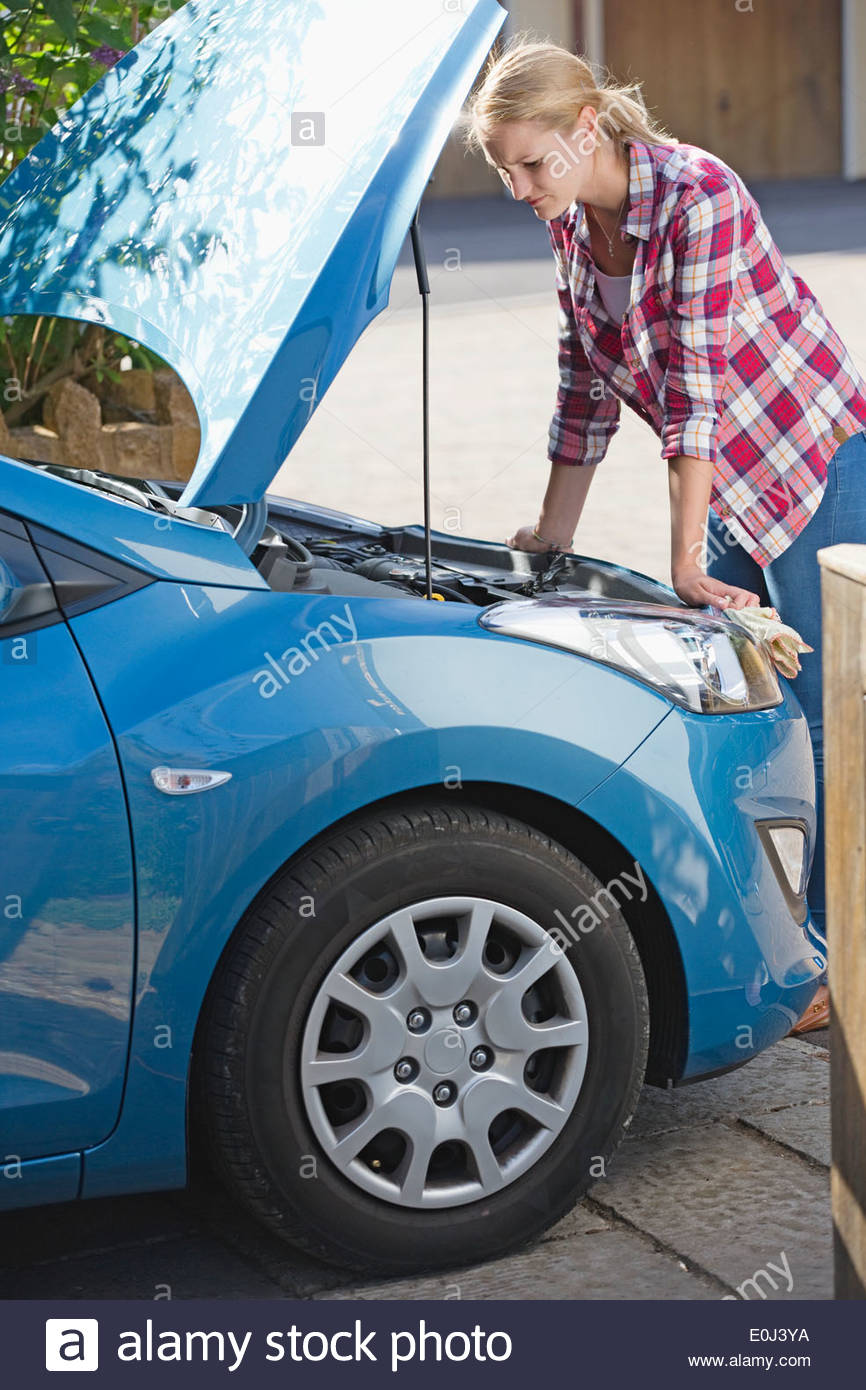 Frau mit aufgeschlüsselt Auto suchen unter Motorhaube Stockbild