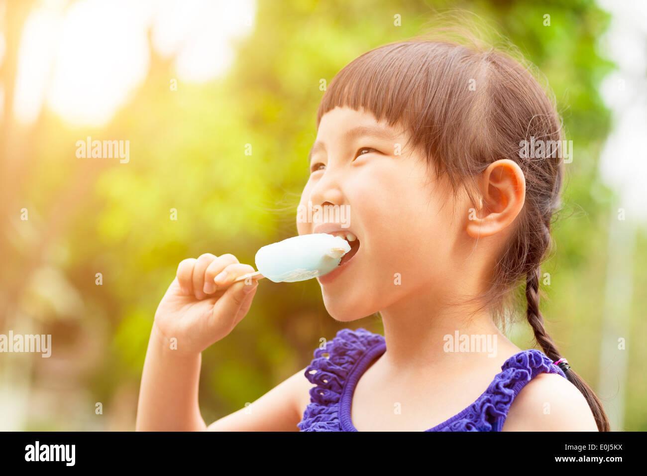 glückliche kleine Mädchen essen Eis am Stiel im Sommer mit Sonnenuntergang Stockfoto