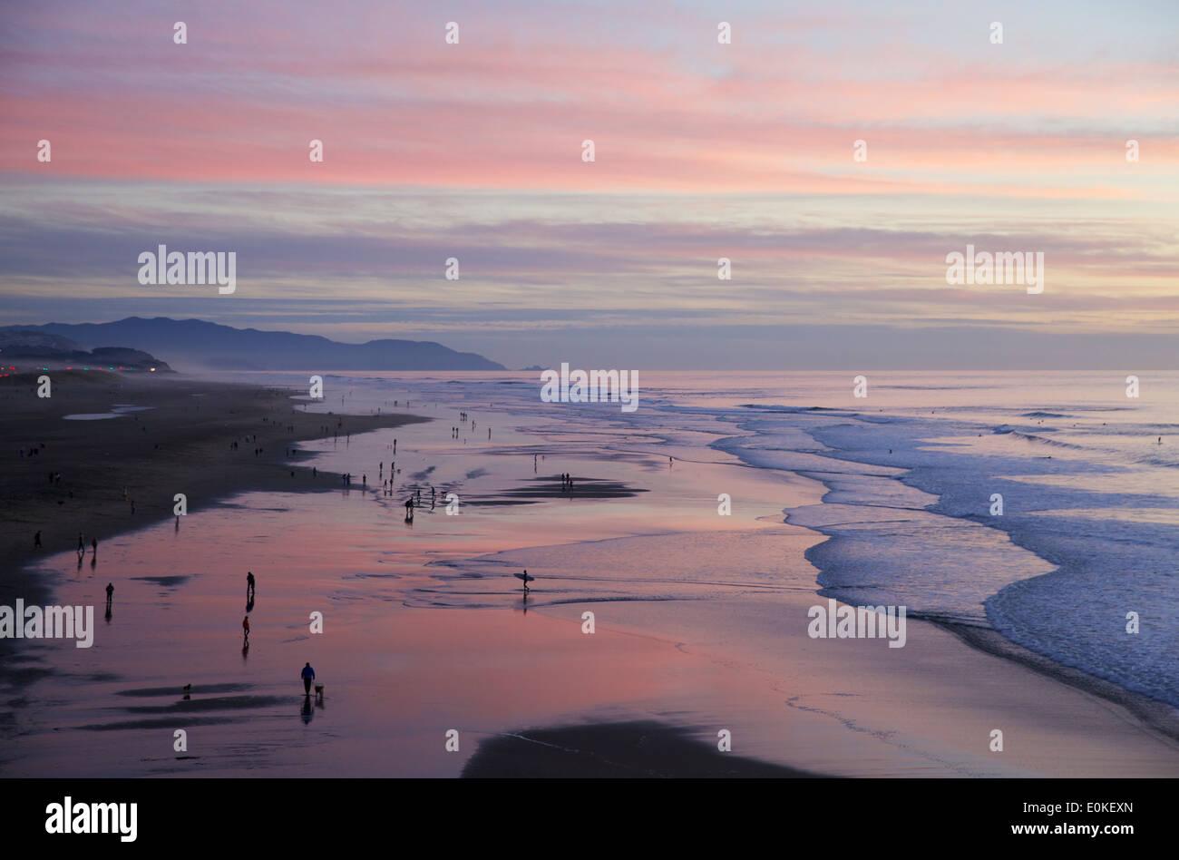 Menschen zu Fuß entlang der Küste sind gegen einen genialen Sonnenuntergang mit Farben blau, rosa und Stockbild