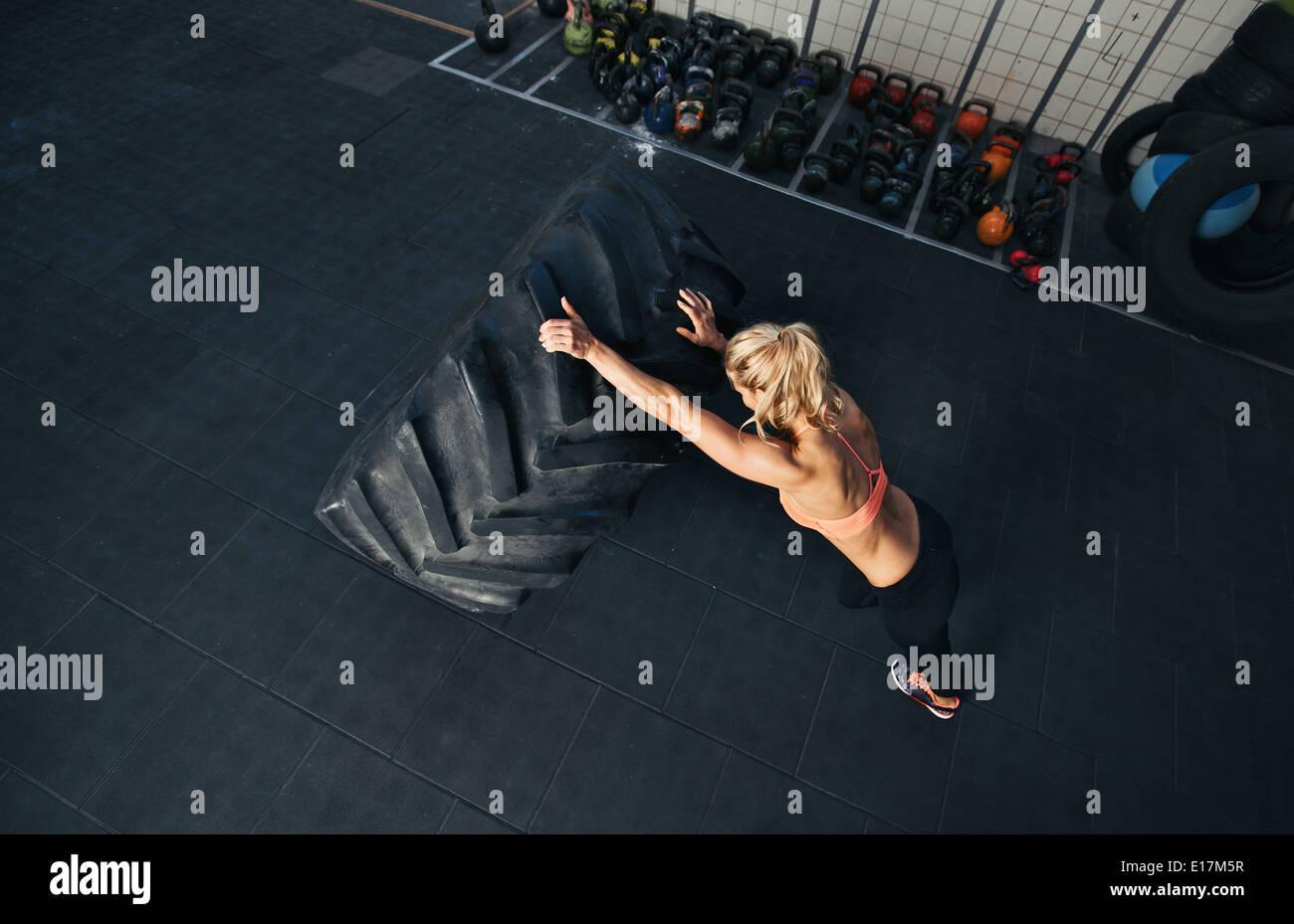 CrossFit Frau im Fitness-Studio trainieren. Muskulöse Frauen spiegeln sehr großer Gummireifen Stockbild