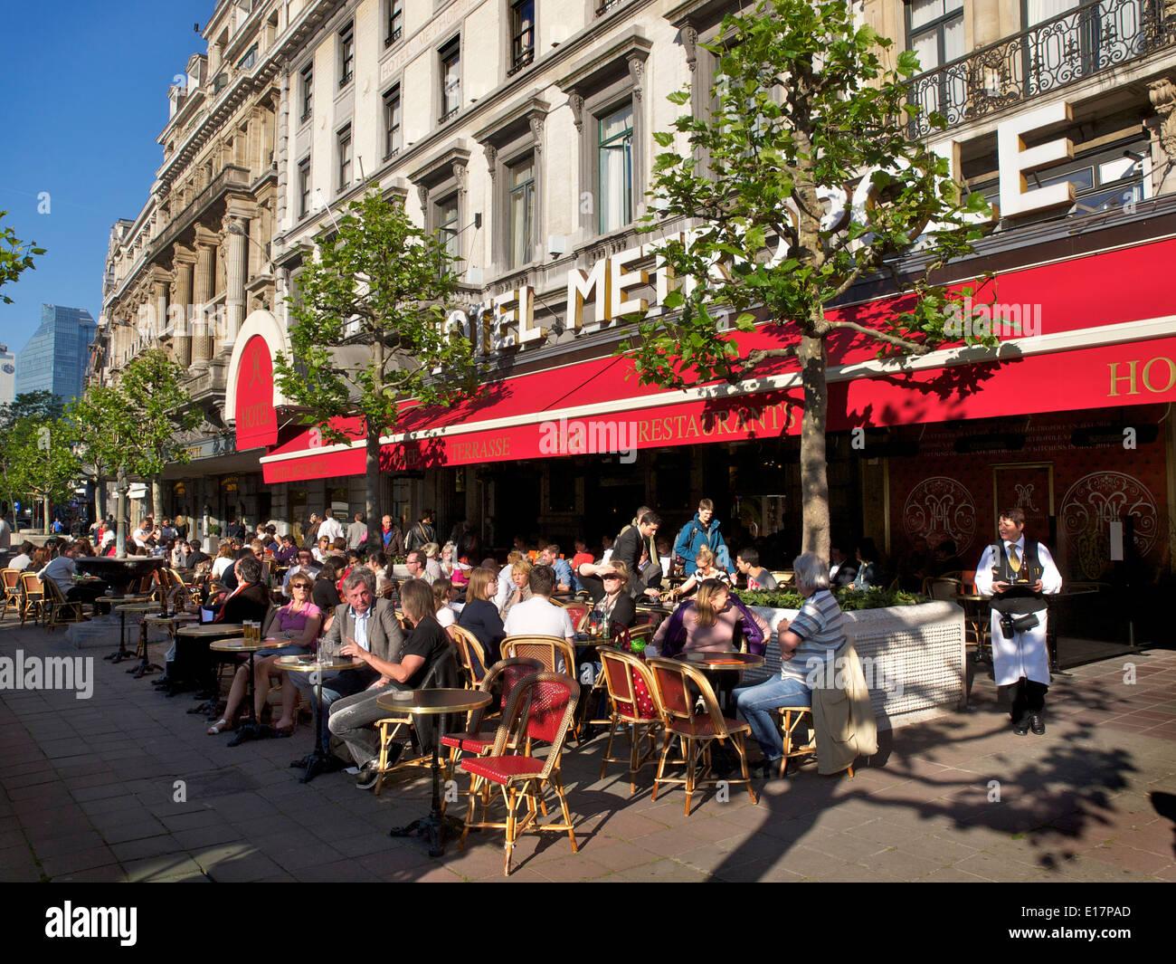 Menschen genießen die Nachmittagssonne vor dem berühmten Hotel Metropole in Brüssel, Belgien Stockbild