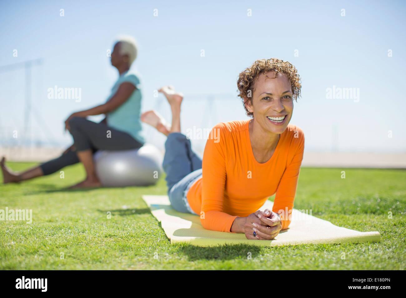 Porträt von lächelnden Frau auf der Yoga-Matte im park Stockbild