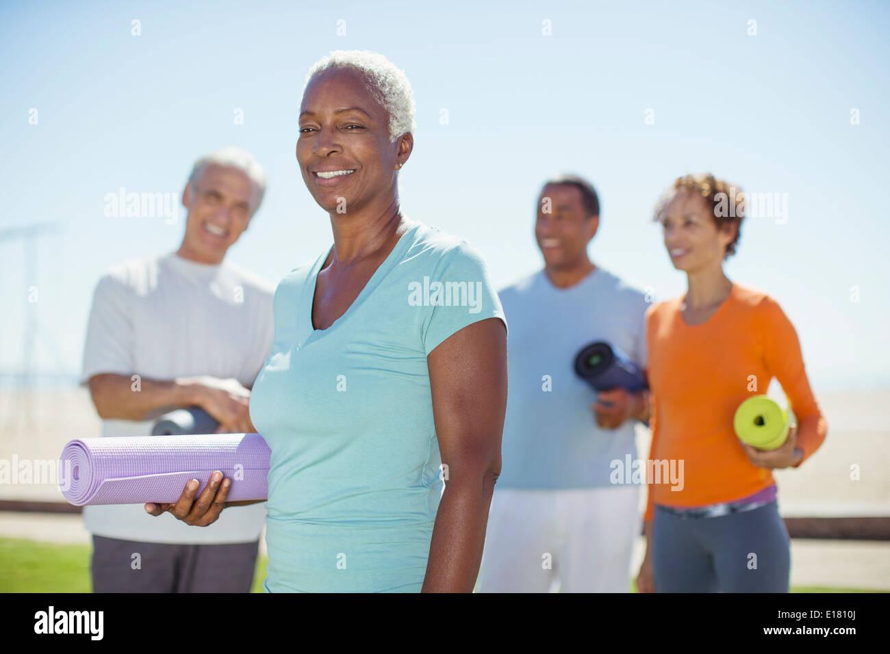 Porträt der selbstbewusste ältere Frau mit Yoga-Matte im park Stockbild