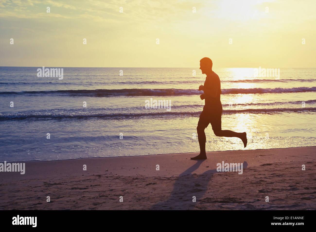 gesunder Lebensstil, Silhouette der Läufer am Strand Stockfoto