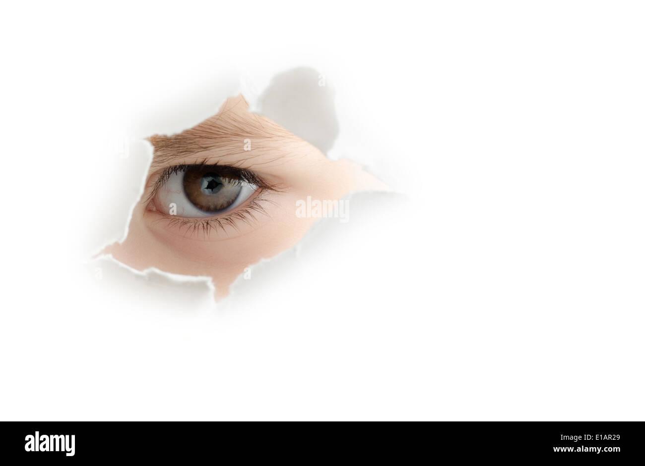 Ein neugieriges Kind ist durch ein Loch in die weiße Wand Spionage. Stockbild