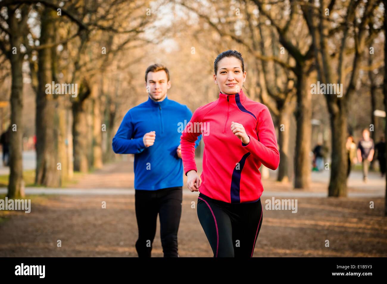 Paar - junger Mann und Frau im Wettbewerb, Frau zuerst Joggen Stockbild