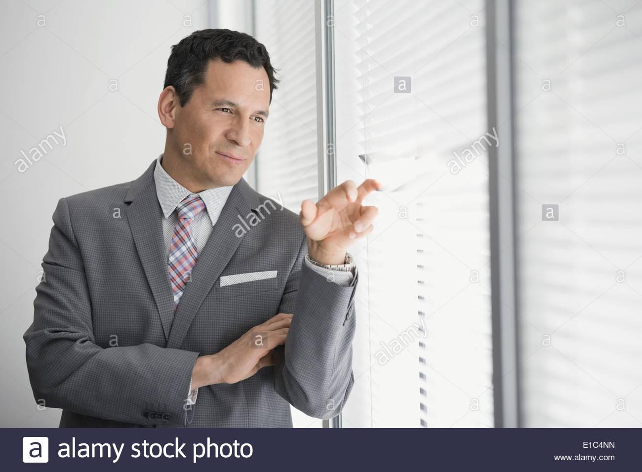 Geschäftsmann spähte durch Jalousien Bürofenster Stockbild