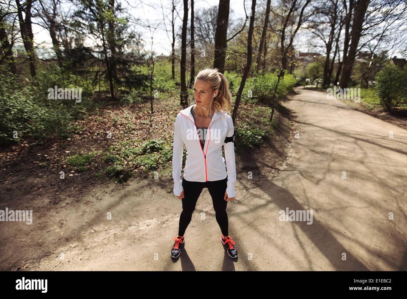 Junge Frau in Ausübung Kleidung stehend auf einem Waldweg wegsehen. Fitness Frauen auf im freien Trainings. Stockbild
