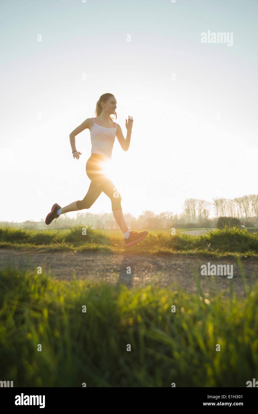 Junge weibliche Läufer auf sonnigen Feldweg Stockbild