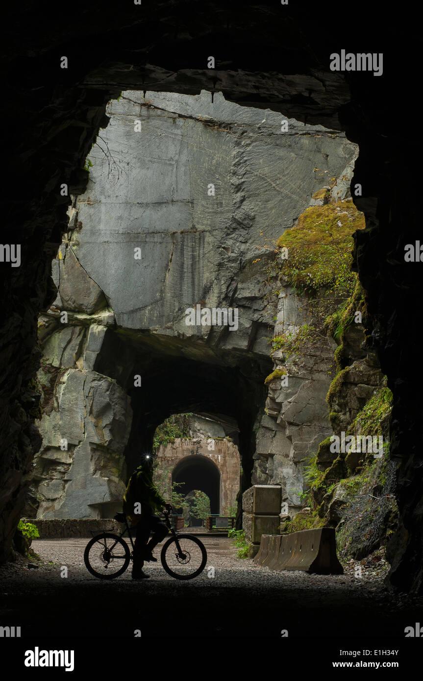 """Radfahrer im Inneren eines Othello Tunnels, Coquihalla Provincial Park, """"KVR"""" Trail, Trans-Canada-Trail, Stockbild"""