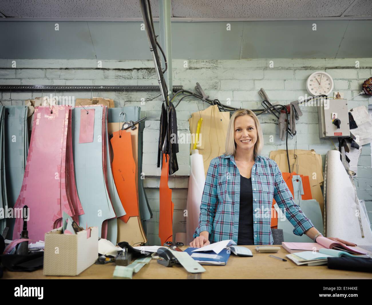 Porträt des Modedesigners schneiden Desk Kleiderfabrik, Lächeln Stockbild