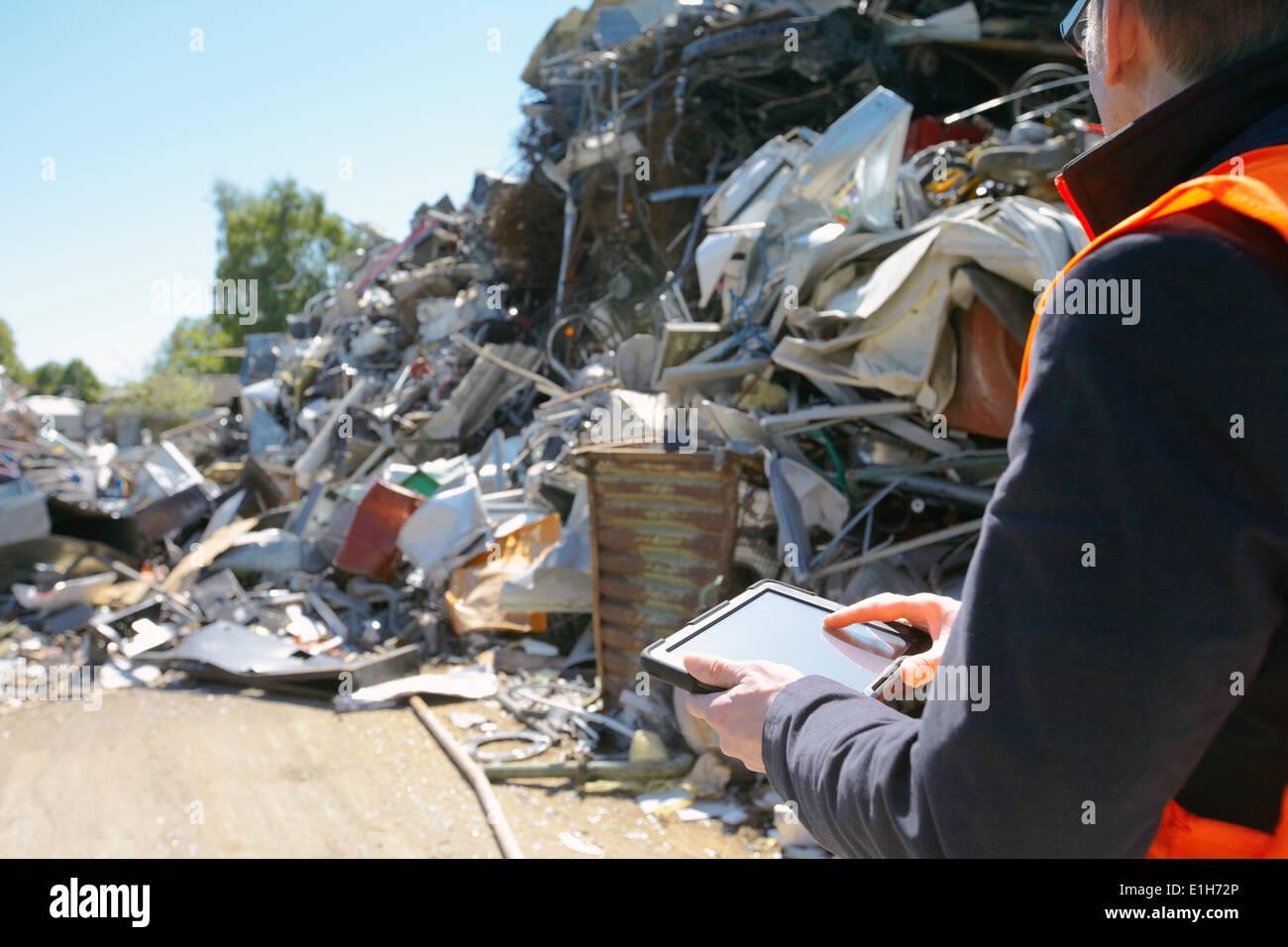 Vorarbeiter mit digital-Tablette am Schrott recycling-Anlage Stockbild