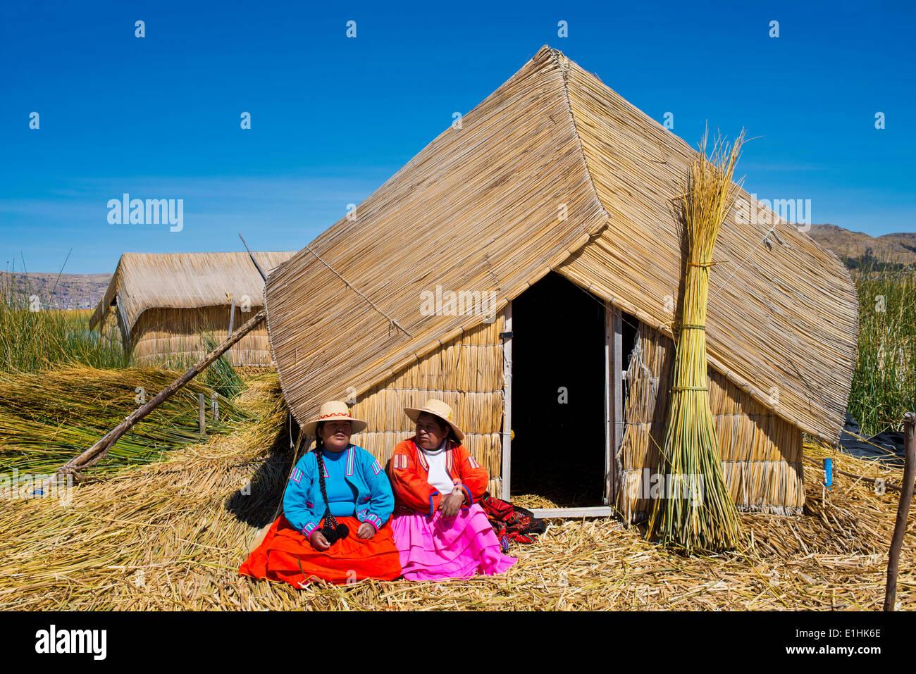 Zwei Frauen der Uro-Indianer tragen traditionelle Kleidung sitzt vor einem Reed-Hütte gemacht schwimmenden Stockbild