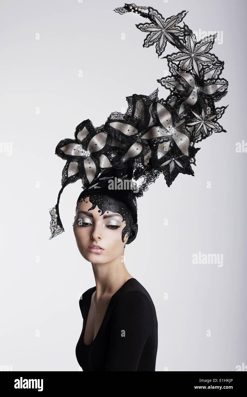 Fantasie. Surrealismus. Erstaunliche Frau in trendige Kopfbedeckung mit Blumen Stockbild