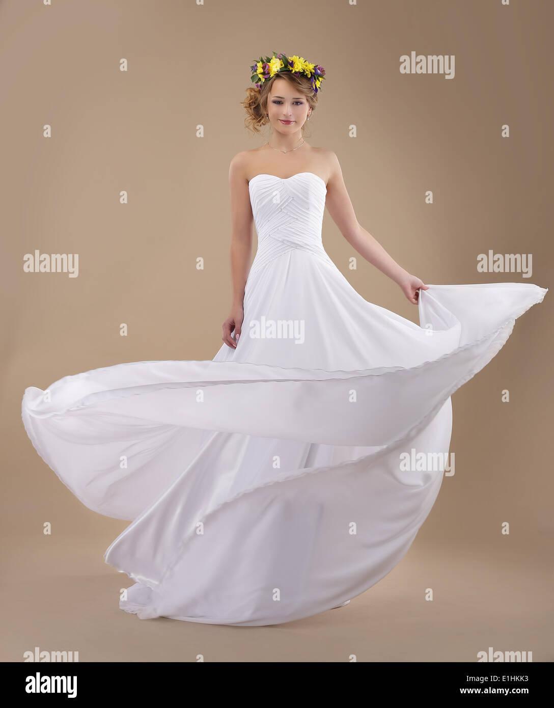Bewegung. Frau mit Kranz aus Blumen und wehenden leichten Kleid Stockbild