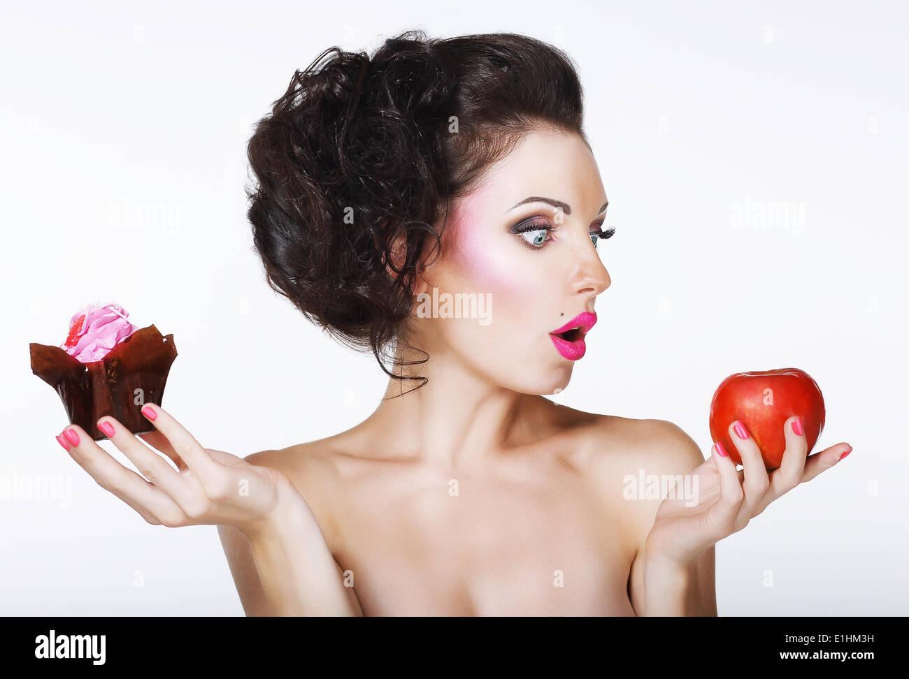 Überrascht, lustige Frau entscheidet zwischen Apple und Kuchen Stockbild