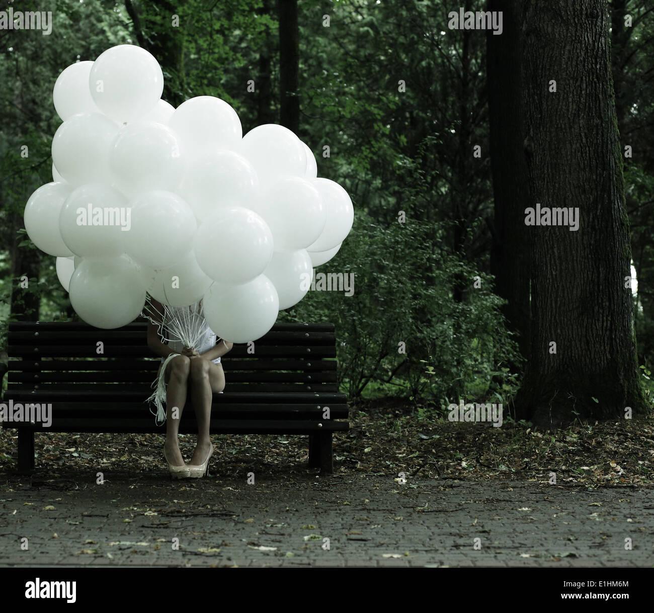 Sentimentalität. Nostalgie. Einsame Frau mit Luftballons auf Bank im Park sitzen Stockbild