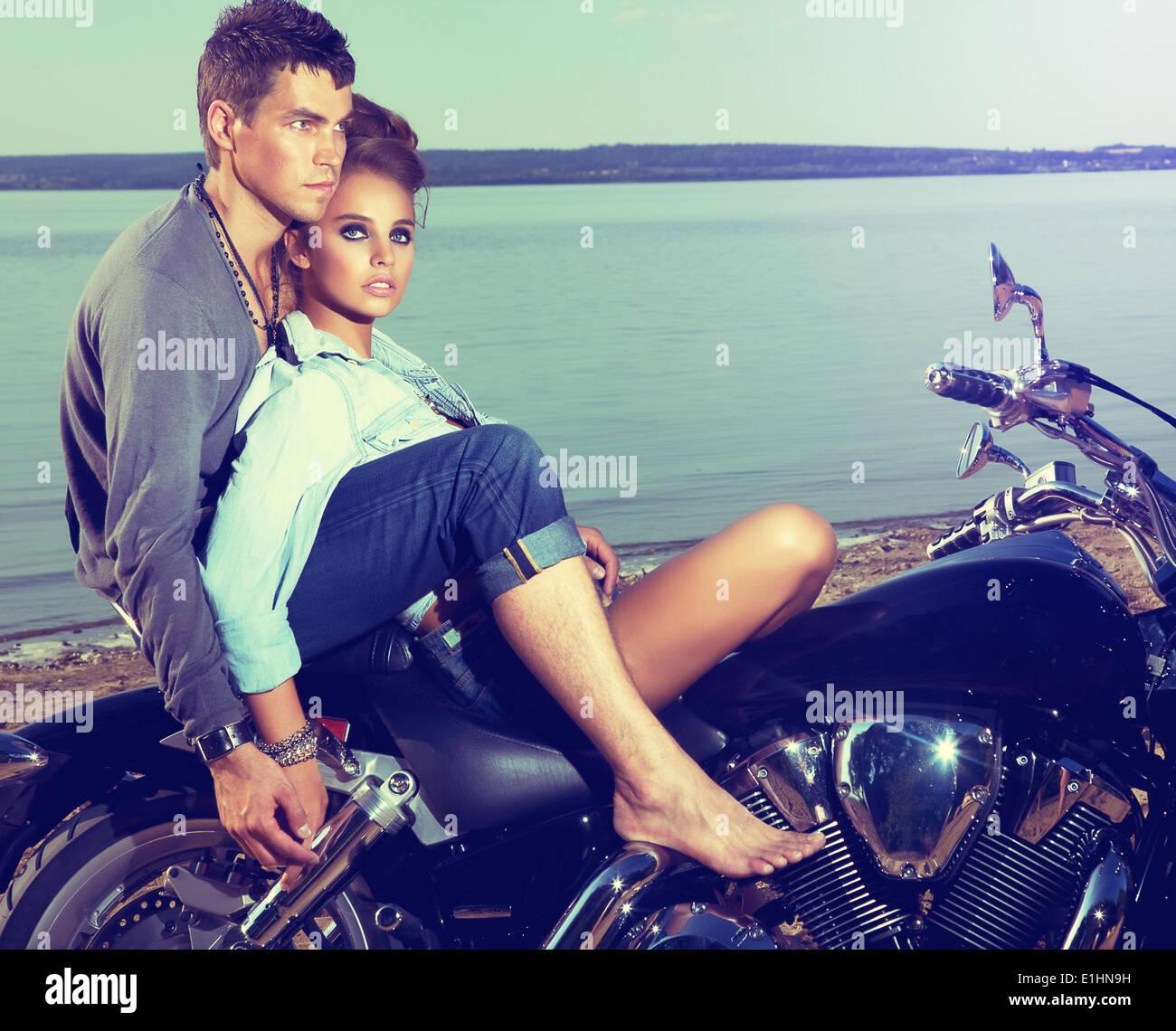 Schönes paar Familie sitzt am Ufer des Sees auf Motorrad Stockbild