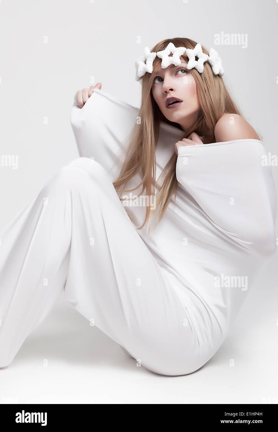 Dramatische theatralische pose - junges Mädchen Schauspielerin in weißen Krone und Kleidung sitzen. Serie Stockbild