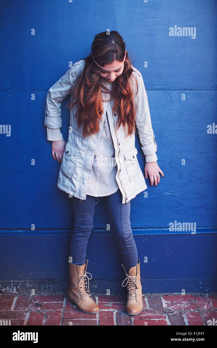 Junge Frau, die blaue Wand blickte gelehnt Stockbild