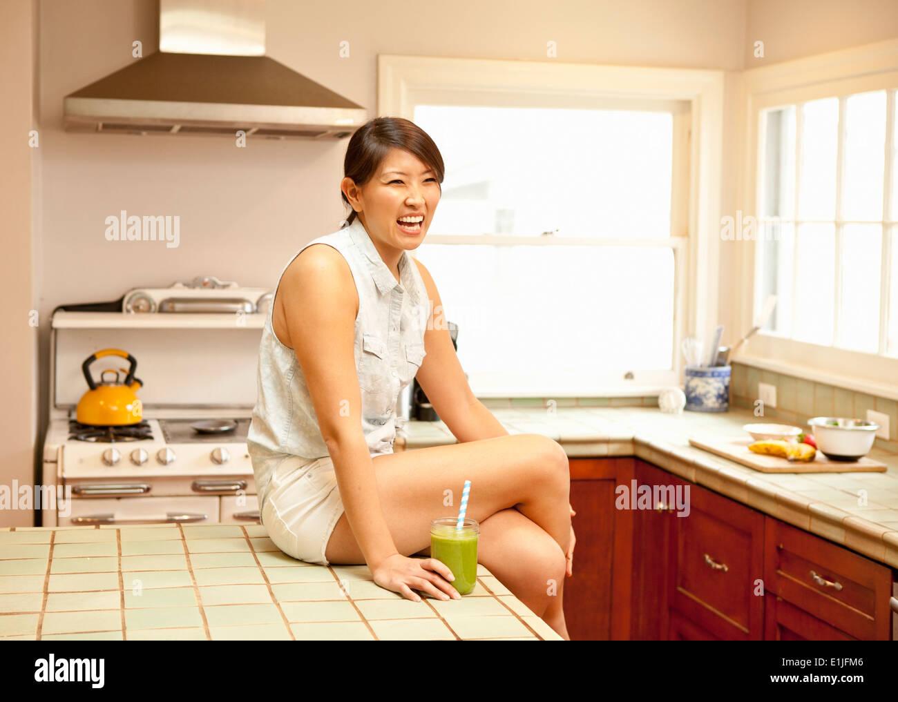 Junge Frau mit grünen Smoothie in Küche Stockbild