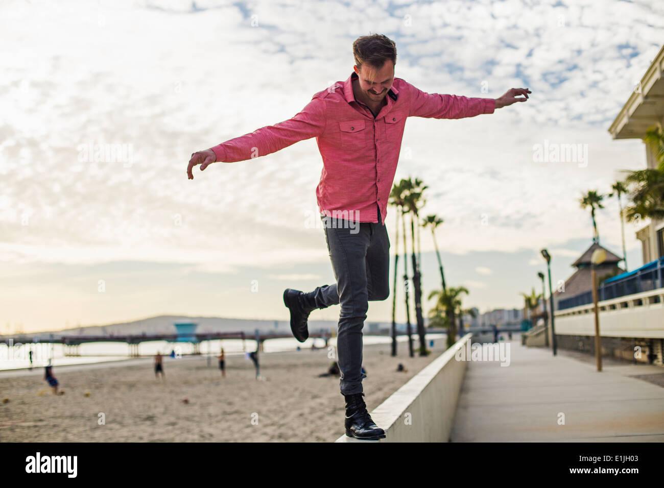 Junger Mann, balancieren auf Wand, Long Beach, Kalifornien, USA Stockbild