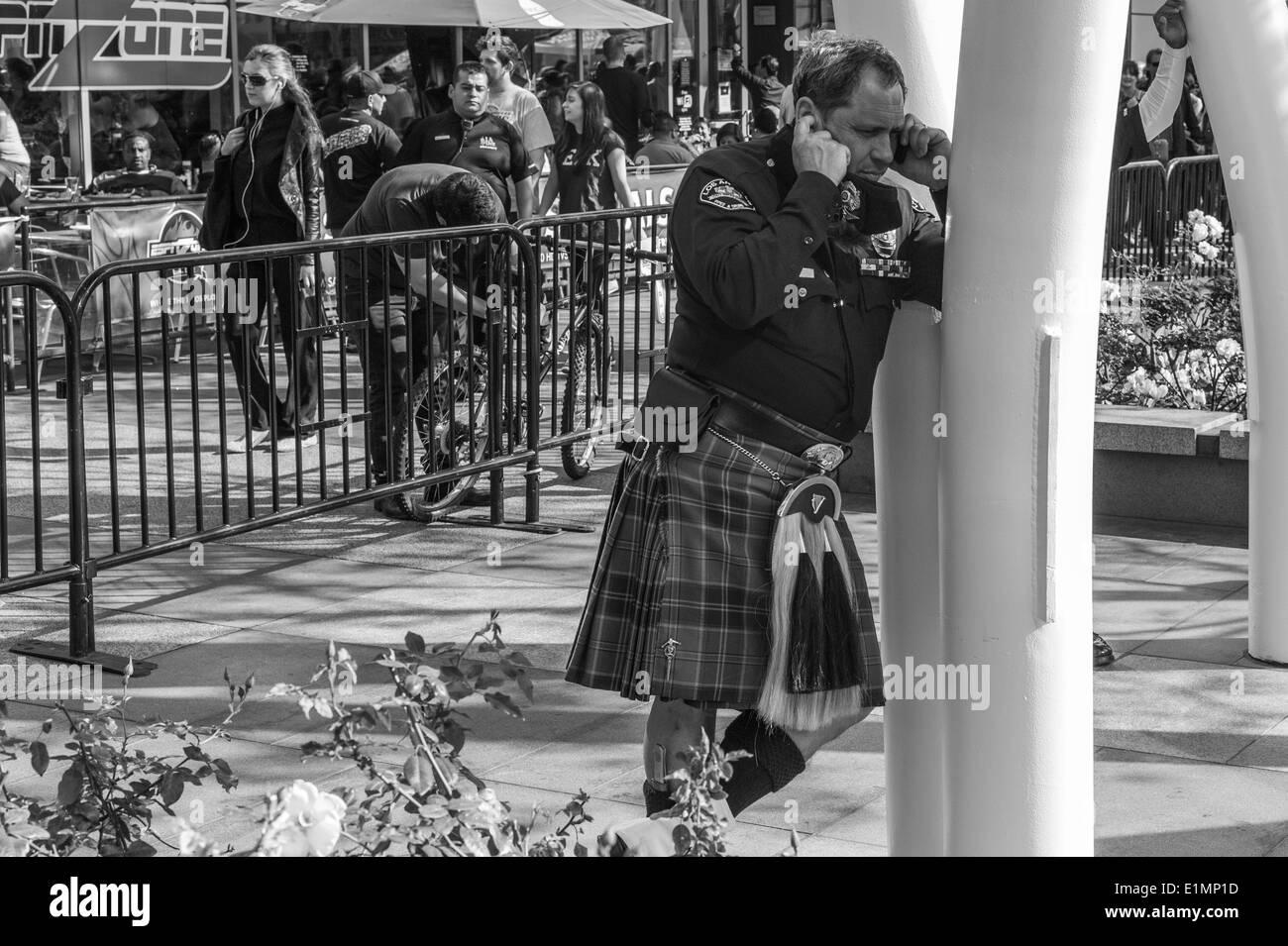 Los Angeles Polizist telefonieren mit Handy am St. Patricks Day Kilt zu tragen. Stockbild