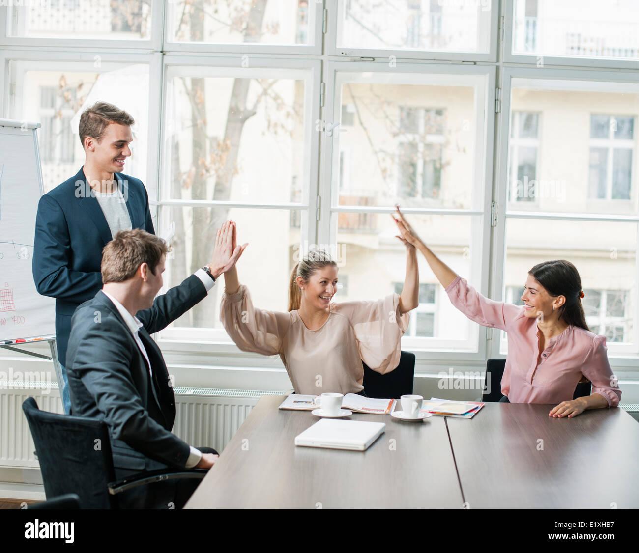 Junges Unternehmen Team dabei hohe fünf am Konferenztisch Stockbild