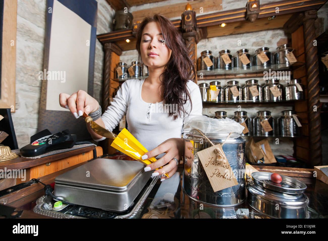 Junger Verkäufer schöpfen Zutat in Papiertüte im Teeladen Stockbild