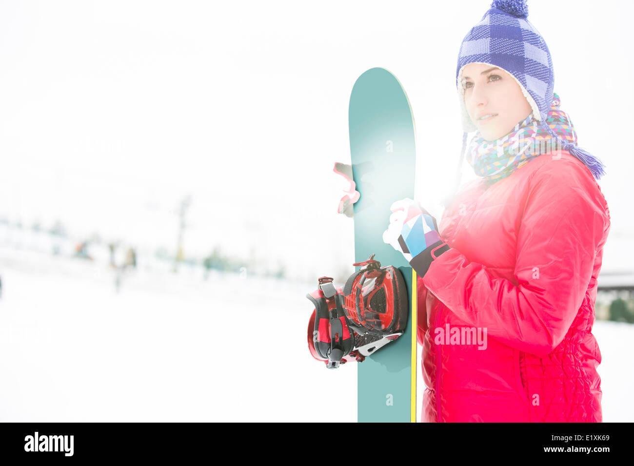 Schöne junge Frau in warme Kleidung hält Snowboard im winter Stockbild
