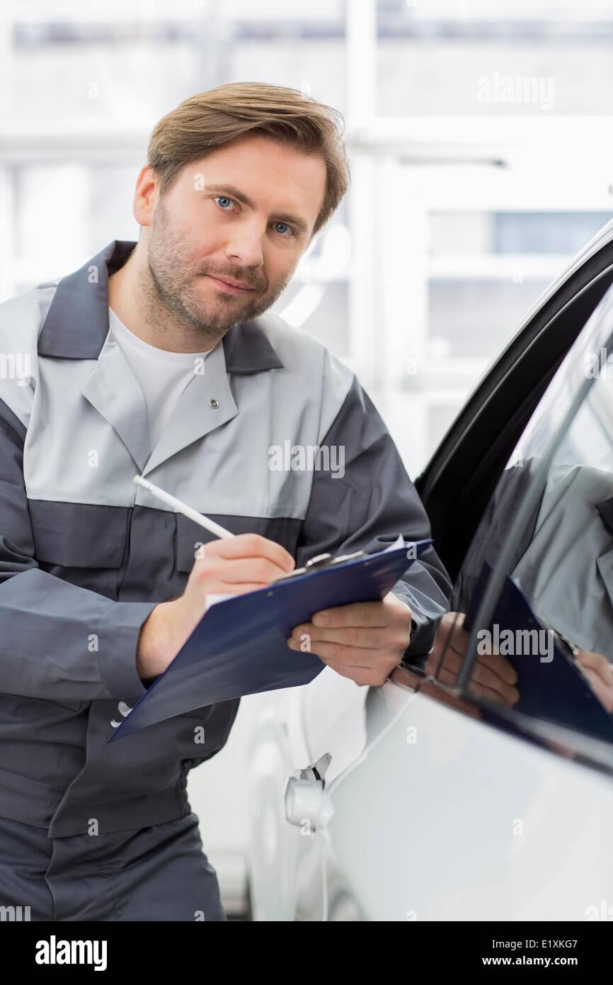 Porträt von zuversichtlich Mechaniker Holding Zwischenablage beim stützte sich auf Autofenster in Werkstatt Stockbild