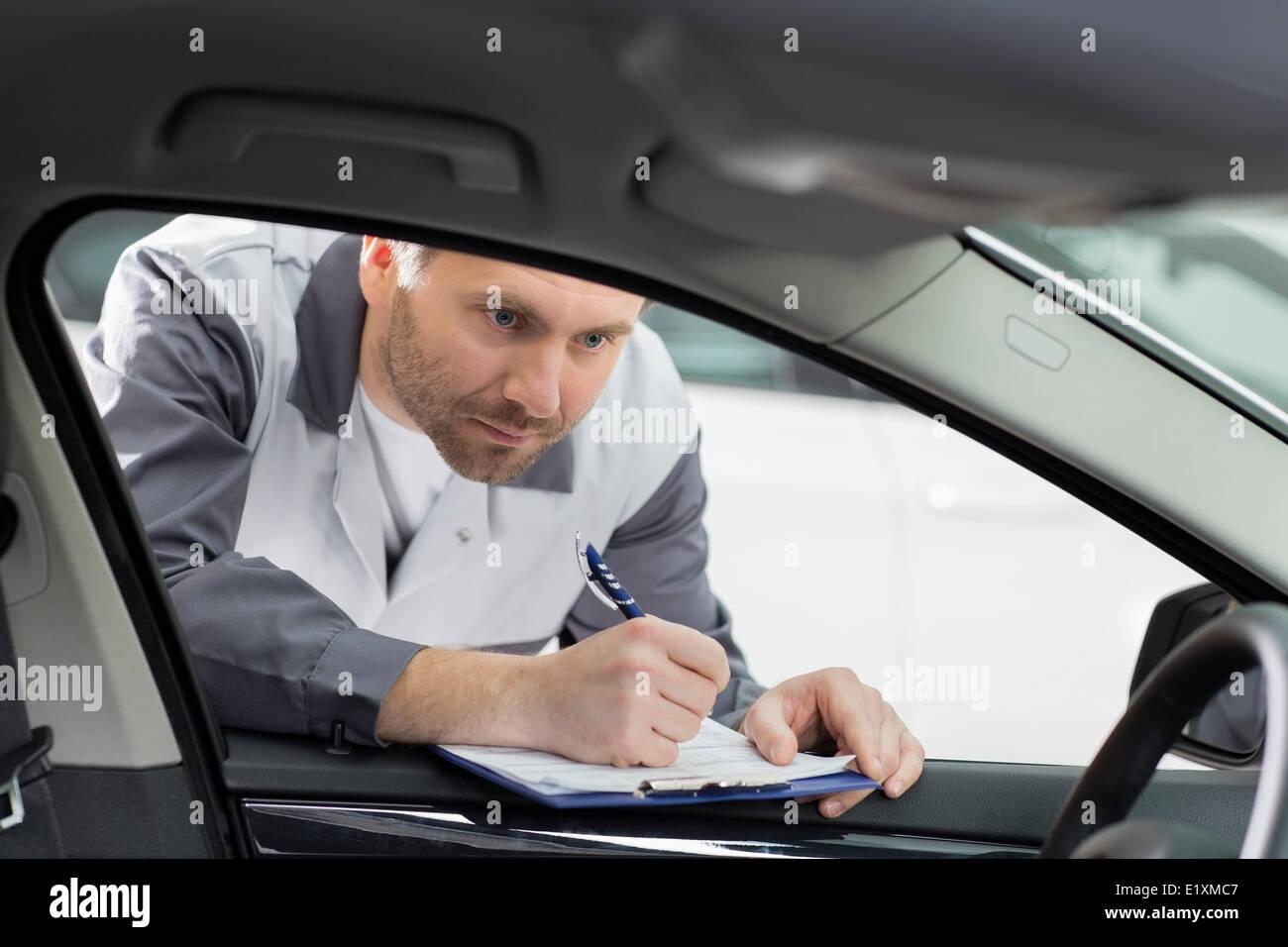Innenraum des männlichen Mechaniker mit Klemmbrett überprüfen Auto Reparaturwerkstatt Stockbild