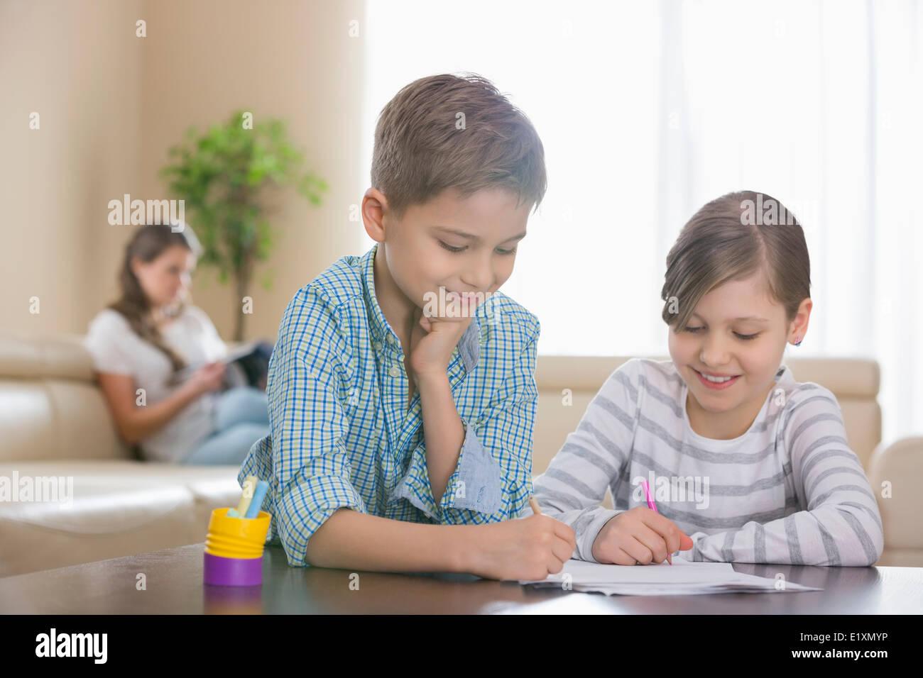 Geschwister, die zusammen am Tisch mit Mutter im Hintergrund zeichnen Stockbild