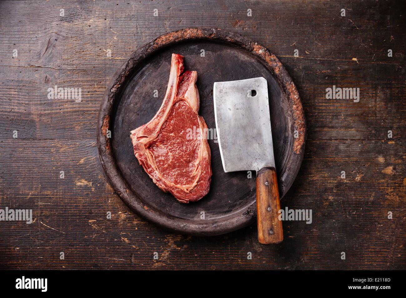 Rohes Frischfleisch Ribeye Steak und Fleischerbeil auf dunklem Hintergrund Stockbild