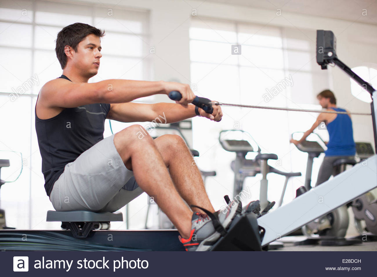 Junger Mann trainieren am Rudergerät im gymnasium Stockbild