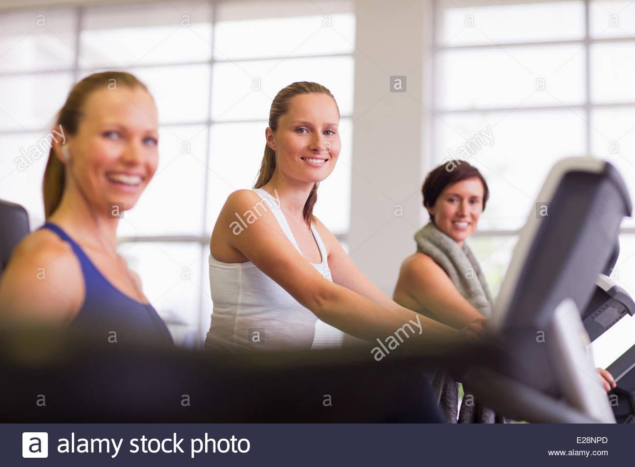 Porträt der lächelnde Frau am Heimtrainer im gymnasium Stockbild