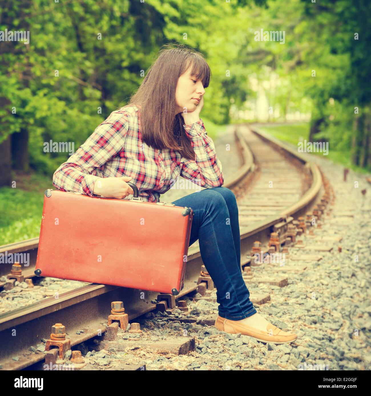 junger Teenager trauriges Mädchen mit Koffer sitzen auf den Schienen Stockbild
