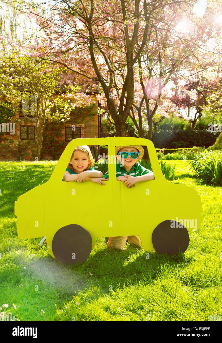 Jungen und Mädchen auf der Suche aus Pappe Autofenster Stockbild