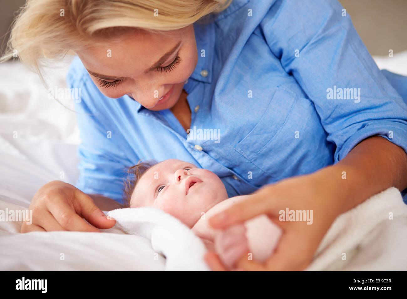 Mutter mit Babymädchen spielen, als sie zusammen im Bett liegen Stockbild
