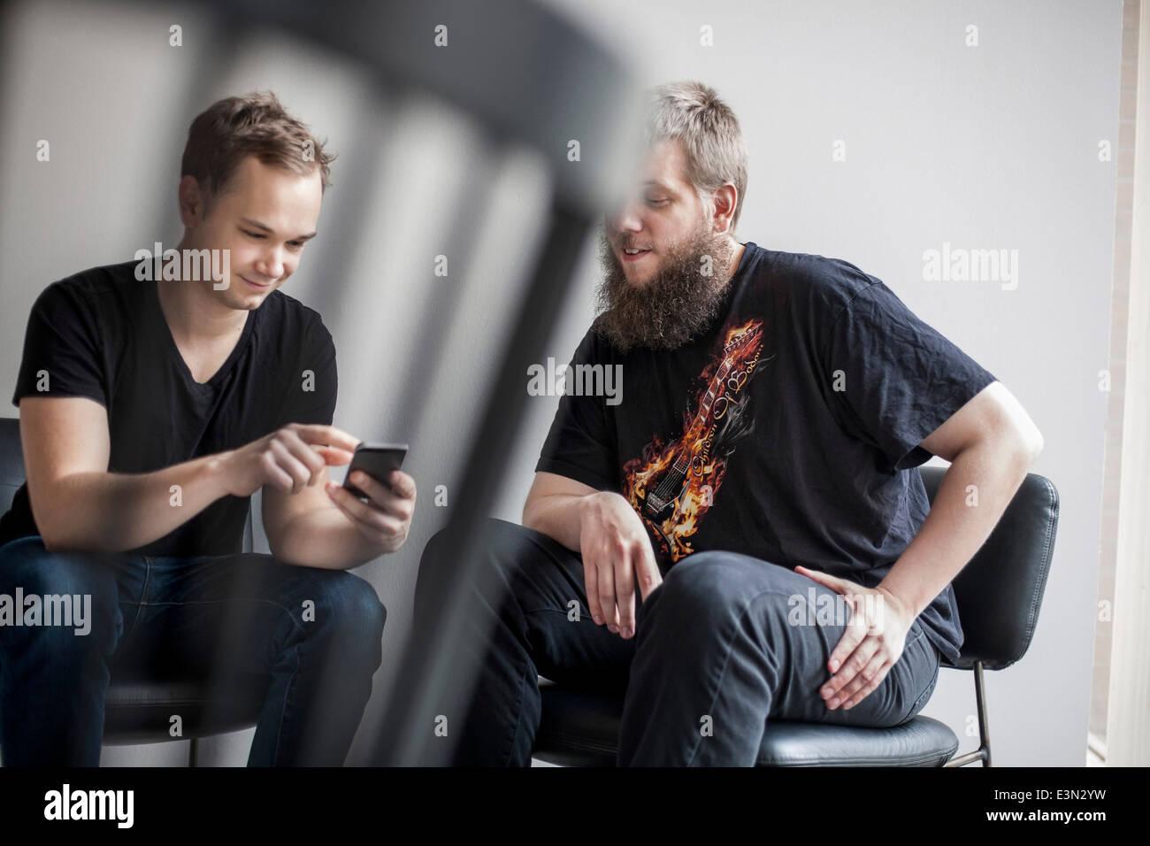 Geschäftsleute, die mit Handy in Kreativbüro Stockbild