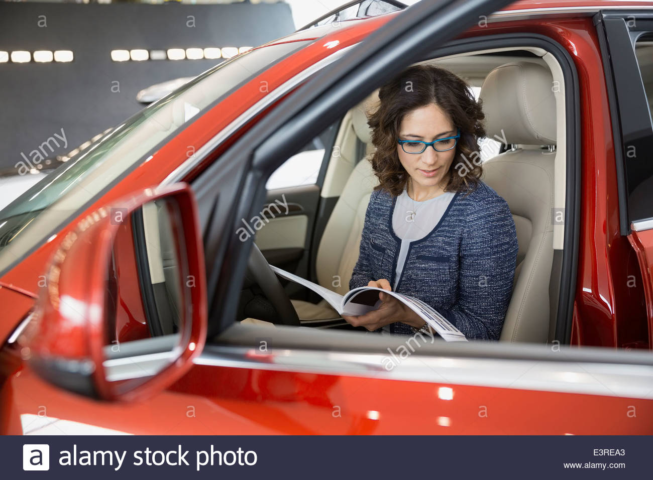 Frau betrachten Broschüre Fahrzeug beim Vertragshändler Stockbild