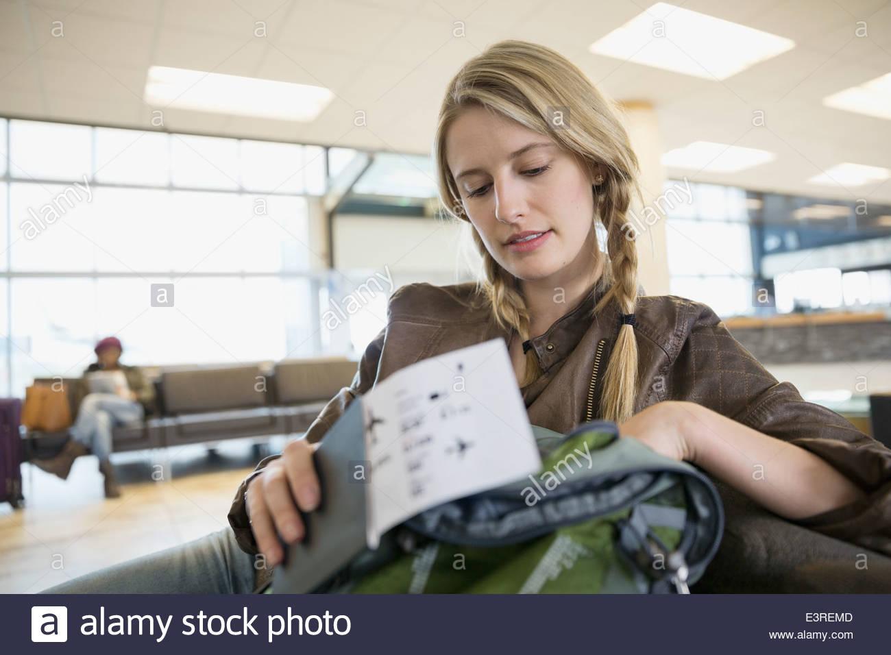 Frau auf der Suche im Rucksack am Flughafen Stockbild