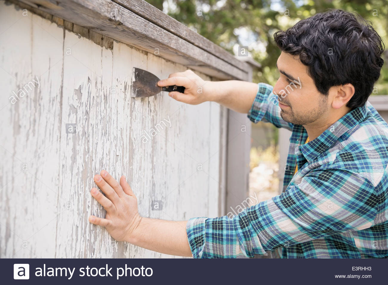 Mann, chipping Farbe vom Holzzaun Stockbild
