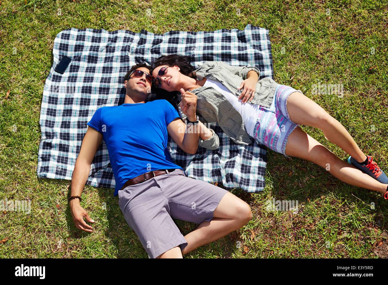 Draufsicht auf paar Hand in Hand auf der Picknickdecke Stockbild